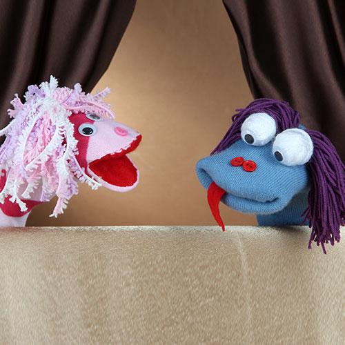 Marioneta azul sacando la lengua y marioneta rosa hablando del Show de Marionetas.