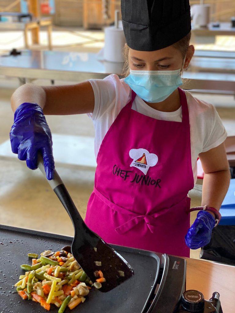 Niña cocinando verduras vestida de cocinera en el Campamento Chef de Sendaviva.