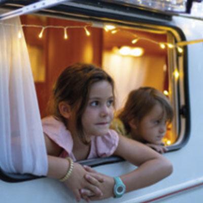 Niños asomándose a la ventana de una autocaravana.