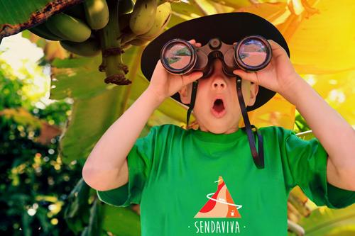 Niño con prismáticos y camiseta de Sendaviva, explorando en los Campamentos de Sendaviva.