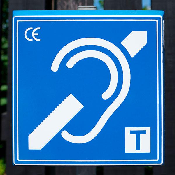 Cartel que indica disponibilidad de bucles magnéticos de inducción para personas con audífonos o implantes cocleares.