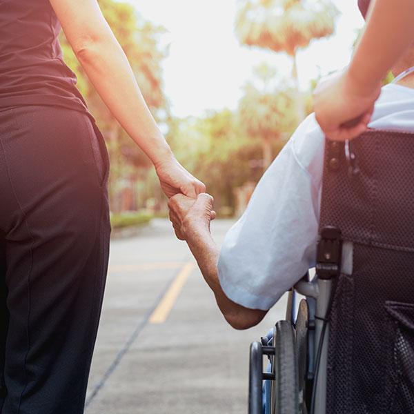 Personal formado de Sendaviva acompañando a una persona en silla de ruedas.