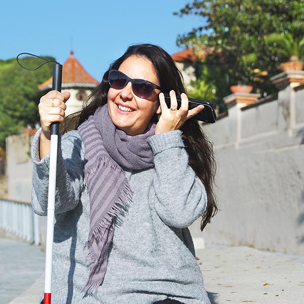 Mujer ciega con un bastón blanco usando el móvil para escuchar desde un lector de pantalla la web de Sendaviva